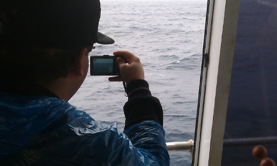 A CNU student stands by to snap a humpback whale surfacing on its migration north.