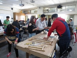 Professor Sun Tzu-Yi guides students in the production of wooden toys
