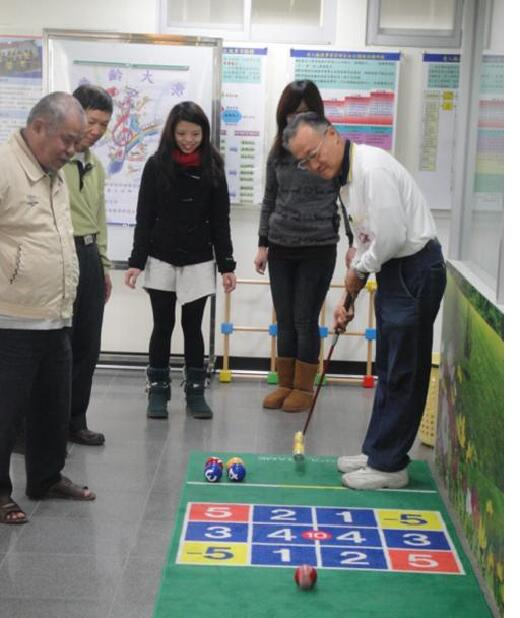 Students leading elderly citizens in a croquet activity
